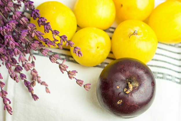 Tas de bouquet de prunes rouges jaunes organiques juteuses mûres de fleurs de lavande sur blanc Photo Premium