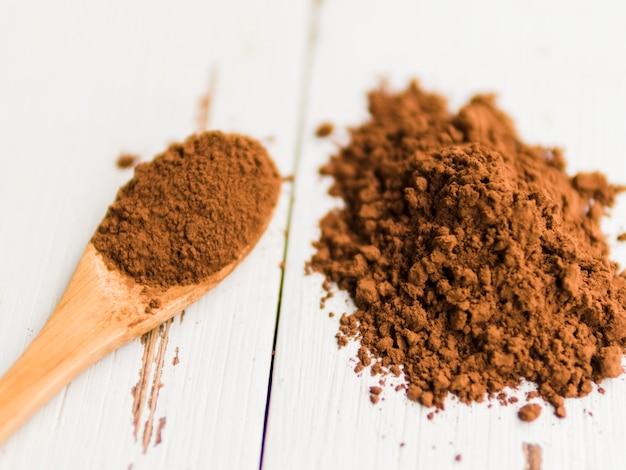Tas de cacao en poudre sur la table et dans la cuillère en bois Photo gratuit