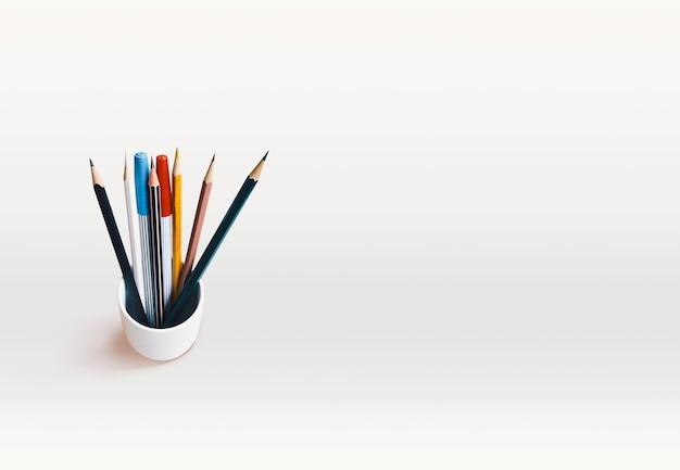 Un tas de crayons a mélangé des stylos de couleurs et magiques sur fond blanc avec espace de copie. Photo Premium