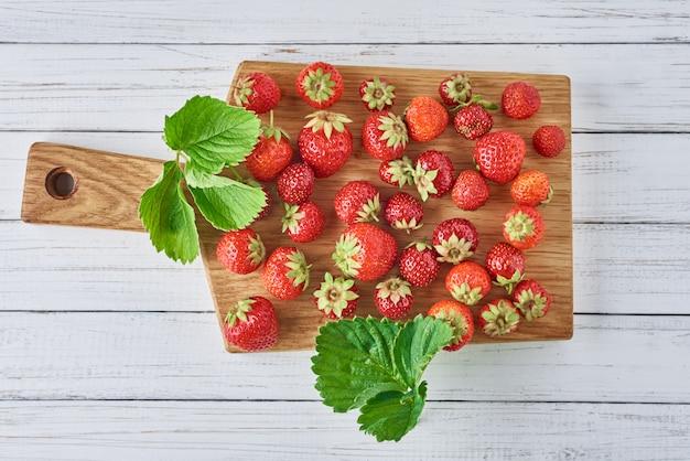 Tas de fraises fraîches avec planche à découper sur une vue de dessus en bois blanche. alimentation saine Photo Premium