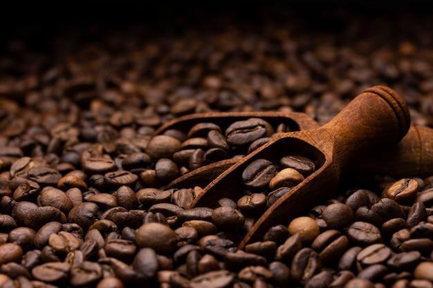 Tas de grains de café avec une cuillère en bois, gros plan, fond sombre avec espace de copie Photo Premium