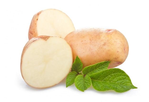 Tas de légumes mûrs de pommes de terre avec des feuilles vertes Photo Premium