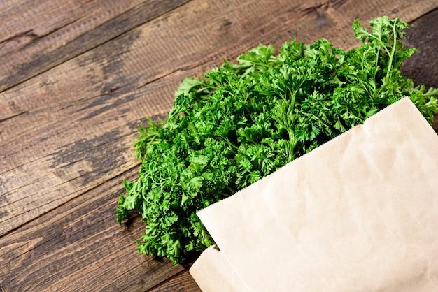 Tas De Légumes Verts Frais, Persil Dans Un Sac En Papier écologique Sur Un Fond En Bois Avec Espace Copie En Gros Plan Photo Premium