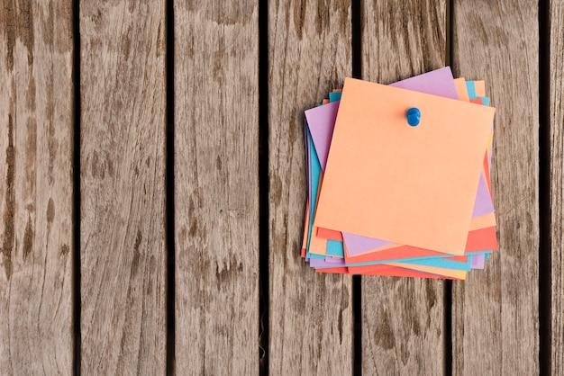 Tas de notes autocollantes attaché avec une punaise bleue sur une table en bois Photo gratuit