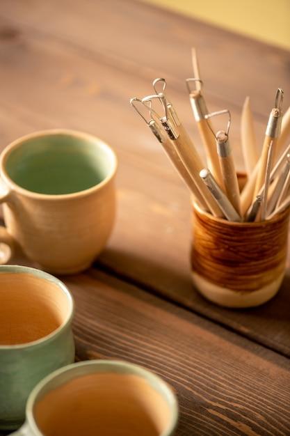 Tas D'outils à Main Spéciaux Pour Travailler Avec De L'argile Et Faire De La Terre Cuite Sur Table En Bois Avec Groupe De Tasses à Proximité Photo Premium