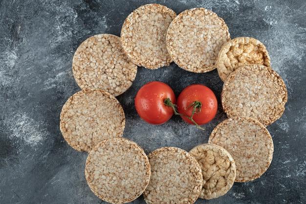 Tas De Pain Croustillant Et De Tomates Fraîches Sur Une Surface En Marbre Photo gratuit