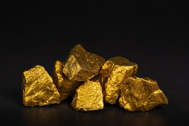 Un tas de pépites d'or ou de minerai d'or sur fond noir, pierre précieuse ou un morceau de pierre dorée, concept financier et commercial. Photo Premium