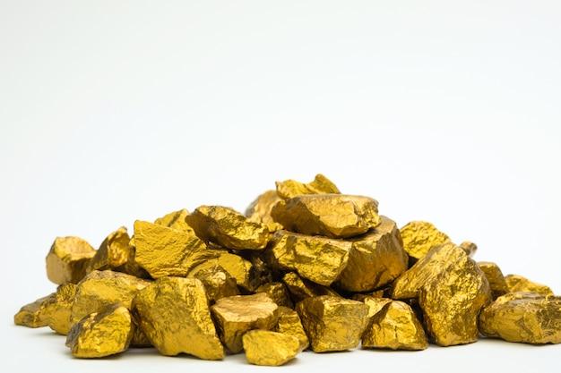 Un tas de pépites d'or ou de minerai d'or isolé sur fond blanc, pierre précieuse ou un morceau de pierre dorée, concept financier et commercial. Photo Premium