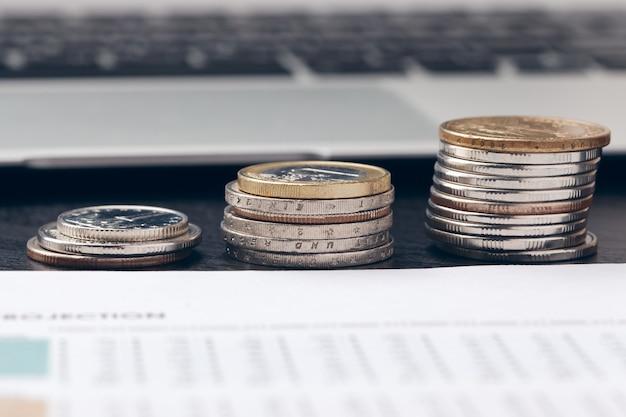 Tas de pièces d'argent avec du papier millimétré sur une table en bois Photo Premium