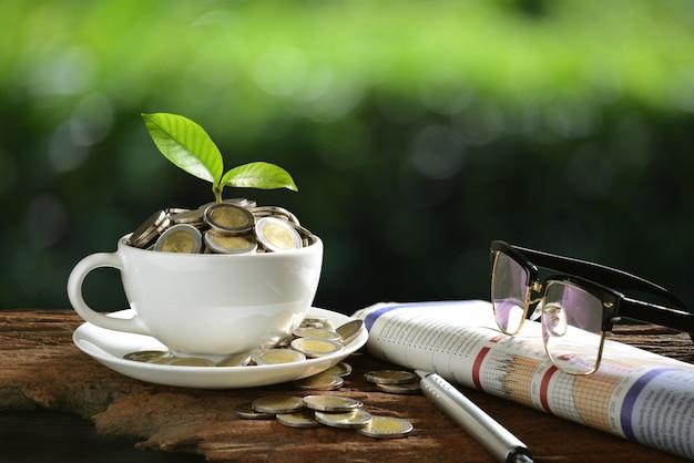 Tas de pièces de monnaie et jeune plante sur le dessus dans une tasse à café avec des journaux et des verres Photo Premium