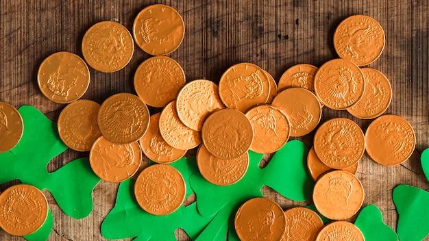 Tas de pièces de monnaie et de trèfles en papier sur une table en bois Photo gratuit