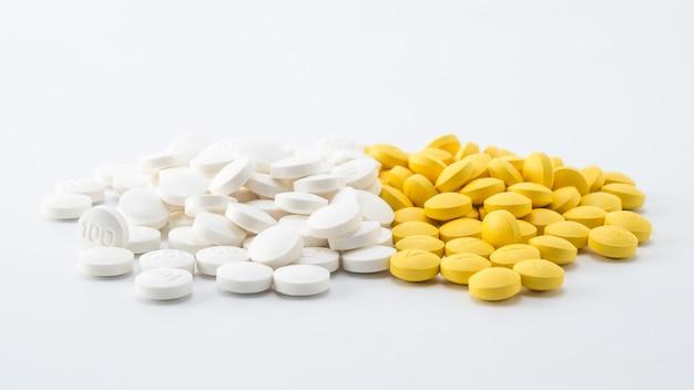 Tas de pilules blanches et jaunes sur fond blanc Photo Premium