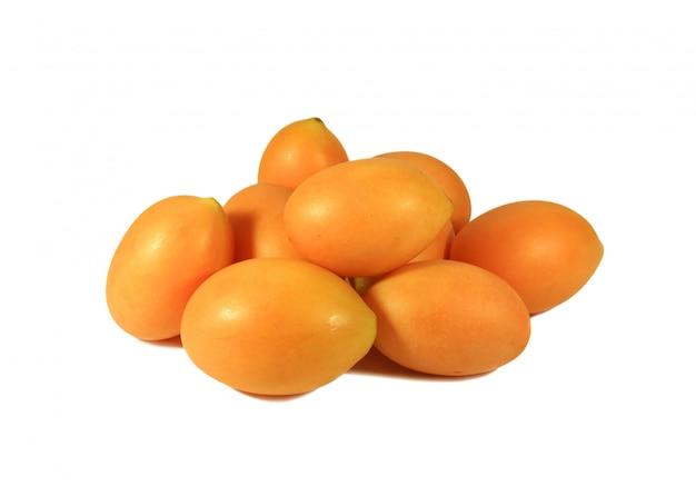 Tas de prune marian mûre vibrante orange jaune frais ou fruits ma-prang isolé sur fond blanc Photo Premium