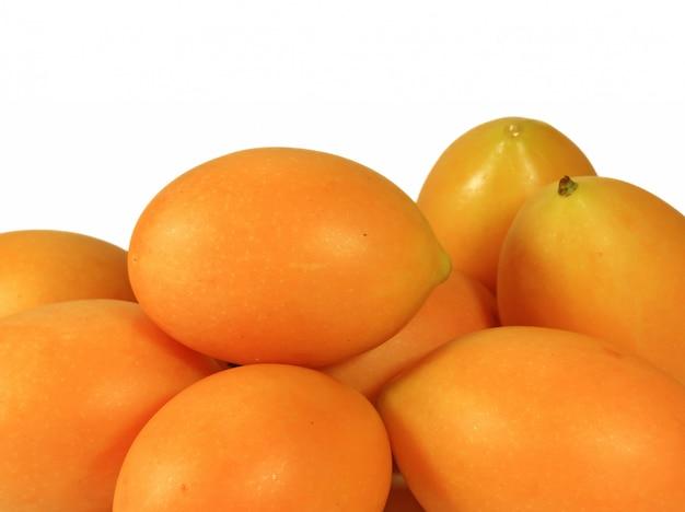 Tas de prunes mariales fraîches jaunes fraîches vibrantes isolées sur fond blanc Photo Premium