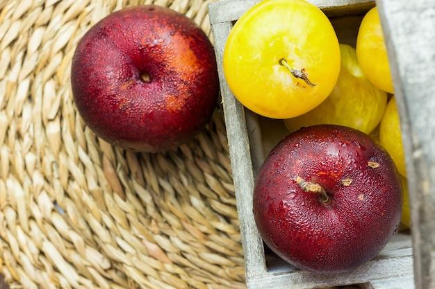 Tas de prunes rouges jaunes organiques juteuses mûres dans une boîte en bois sur rotin Photo Premium