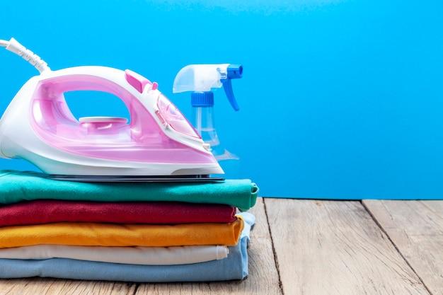 Tas de vêtements colorés et fers à repasser, vaporisateurs, sur une planche de bois Photo Premium