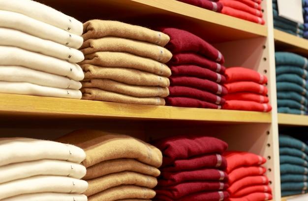 Des tas de vêtements multicolores sur les étagères du magasin Photo Premium