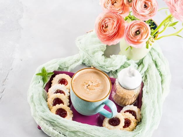 Tasse de biscuits au café et de fleurs de renoncule roses. petit déjeuner festif. saint valentin Photo Premium