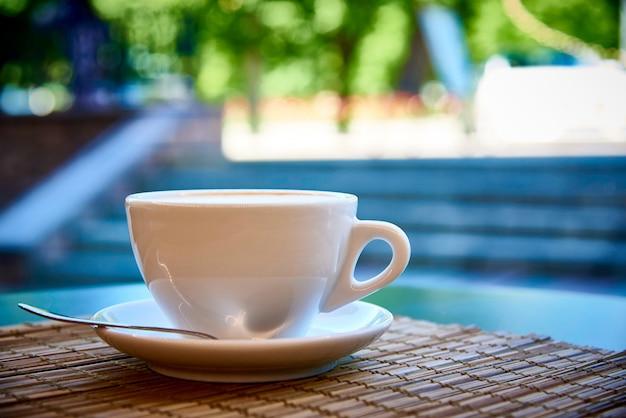 Tasse blanche avec boisson au café sur close-up de serviette en bambou sur fond clair avec bokeh. Photo Premium