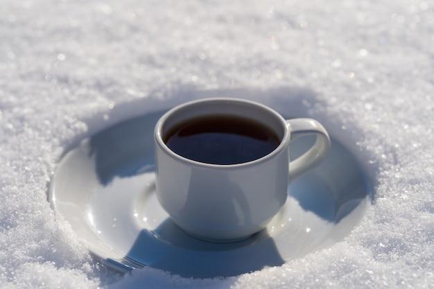 Tasse Blanche De Café Chaud Sur Un Lit De Neige Et Fond Blanc, Gros Plan. Concept De Matin D'hiver De Noël Photo Premium
