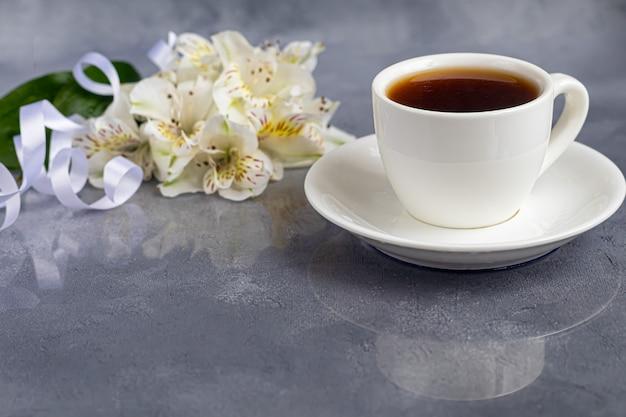 Tasse Blanche Avec Café Sur Fond Gris. Un Bouquet D'orchidées Enlacé Avec Un Ruban En Arrière-plan. Bannières, Félicitations Pour Les Vacances. Copiez L'espace. Photo Premium
