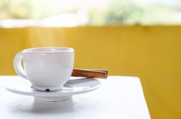 Tasse blanche de café sur une table blanche avec un fond jaune Photo Premium