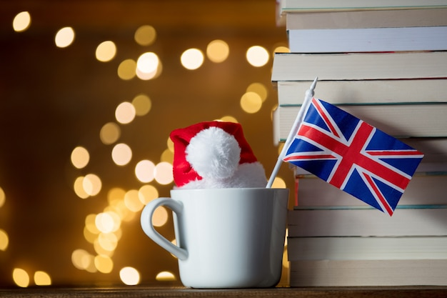 Tasse blanche et chapeau de noël avec le drapeau de la grande-bretagne près de livres Photo Premium
