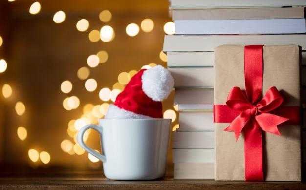 Tasse blanche avec chapeau de noël et des livres Photo Premium