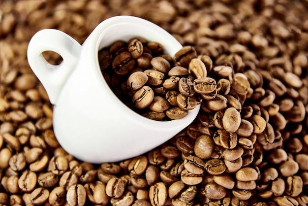 Tasse blanche en grains de café. Photo Premium