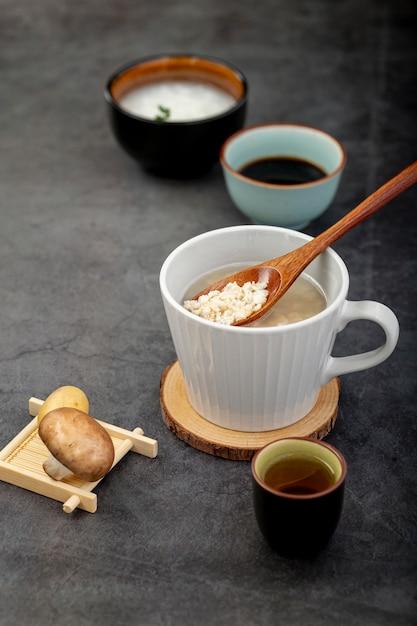 Tasse blanche de soupe sur un support en bois avec un champignon Photo gratuit