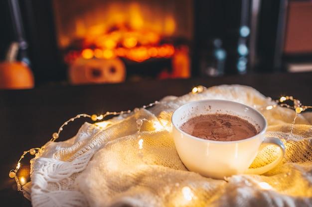 Tasse De Boisson Chaude Devant La Cheminée Chaude. Noël De Vacances. Tasse Blanche Debout Près Du Feu. Atmosphère Magique Détendue Et Confortable Dans Un Chalet. Photo Premium