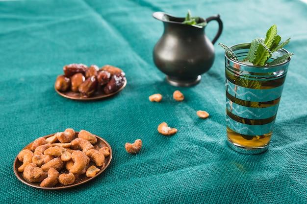 Tasse de boisson près du pichet avec plante, fruits secs et noix Photo gratuit