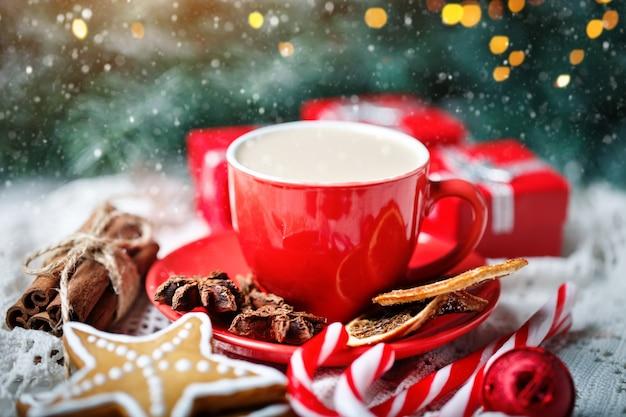 Tasse de cacao, biscuits, cadeaux et branches de sapin sur une table en bois blanche Photo Premium