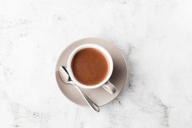 Tasse De Cacao Chaud Ou Chocolat Chaud Ou Americano Dans Une Tasse Blanche Isolée Sur Fond De Marbre Brillant. Vue Aérienne, Espace Copie. Publicité Pour Le Menu Du Café. Menu Du Café. Photo Verticale. Traditionnel Photo Premium