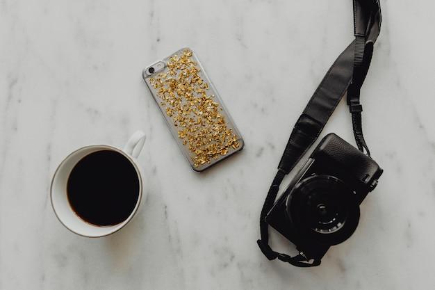 Tasse de café avec un appareil photo reflex numérique et un téléphone Photo gratuit