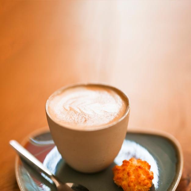 Une tasse de café d'art latte chaud sur un fond texturé en bois Photo gratuit
