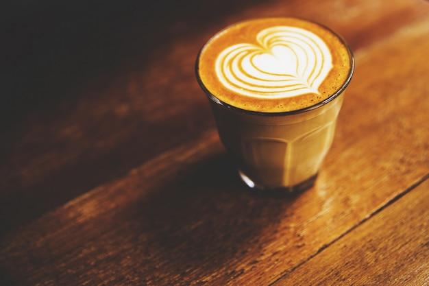 Tasse de café au lait chaud est sur le fond de la table en bois Photo Premium
