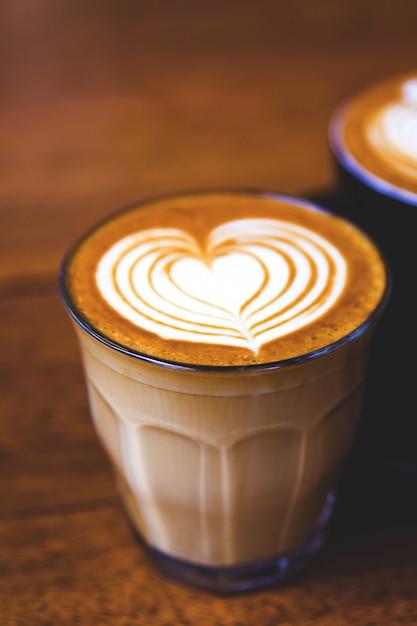 Tasse de café au lait chaud sur une table en bois Photo Premium