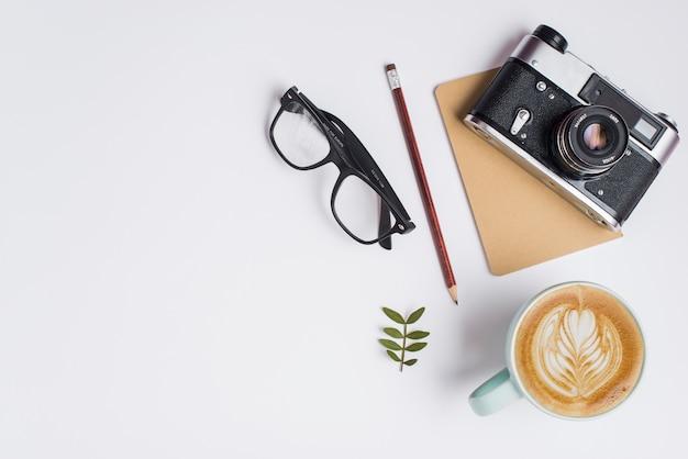 Tasse de café au lait; crayon; lunettes et appareil photo vintage sur fond blanc Photo gratuit