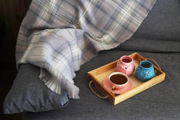 Une tasse de café au lait sur un plateau en bois avec des chandeliers roses et turquoises Photo Premium