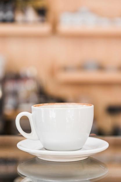 Tasse à café blanche sur comptoir en verre réfléchissant Photo gratuit