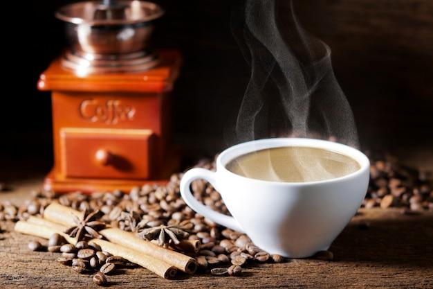 Tasse à café blanche et grains de café torréfiés autour Photo Premium