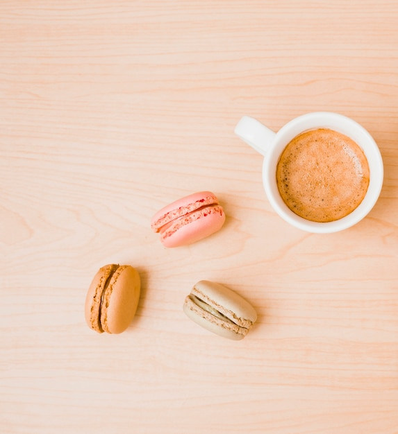 Tasse à café blanche et macarons sur fond texturé en bois Photo gratuit