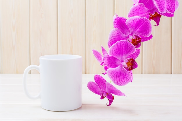 Tasse à café blanche avec orchidée rose Photo Premium