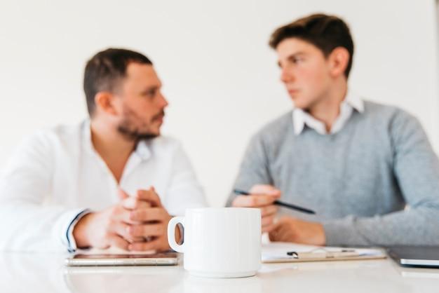 Tasse à café blanche sur la table de bureau Photo gratuit