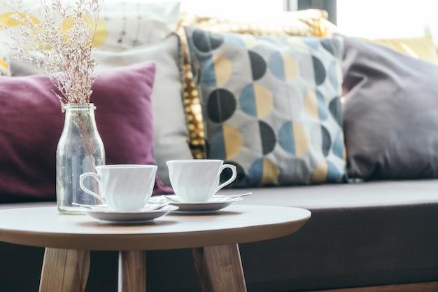 Tasse à café blanche avec vase à fleur sur la décoration de la table avec oreiller sur le canapé Photo gratuit