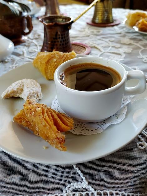 Une Tasse De Café Et Des Bonbons Sur Une Soucoupe, Un Café Dans Un Stand Turc Sur Une Nappe Brodée Blanche. Photo Premium