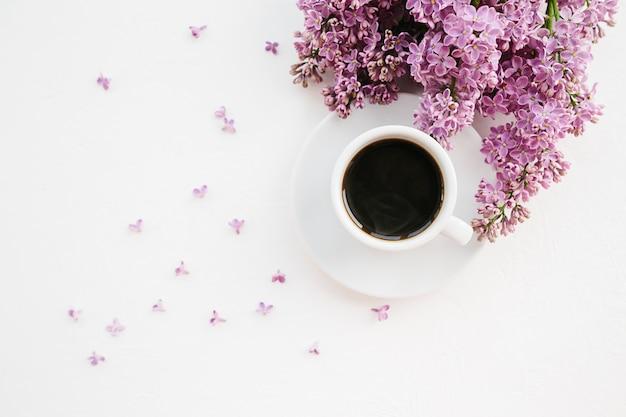 Tasse de café et de branche de lilas sur blanc Photo Premium