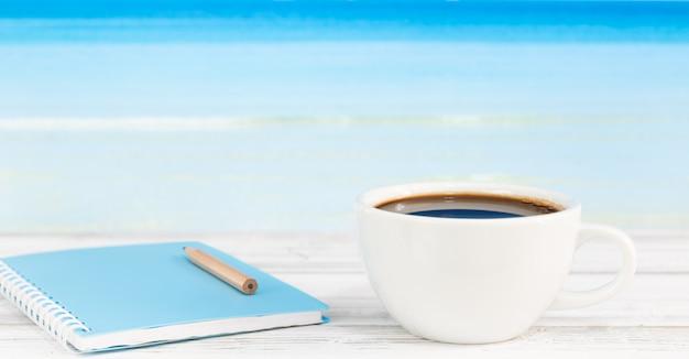 Tasse à café et cahier bleu sur table en bois blanc avec fond de mer brillant Photo Premium