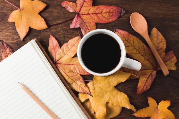 Tasse à café et cahier sur fond de feuilles d'automne Photo gratuit